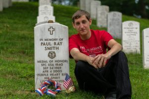A Freedom Alliance Scholarship recipient sits next to his father's grave at Arlington National Cemetery